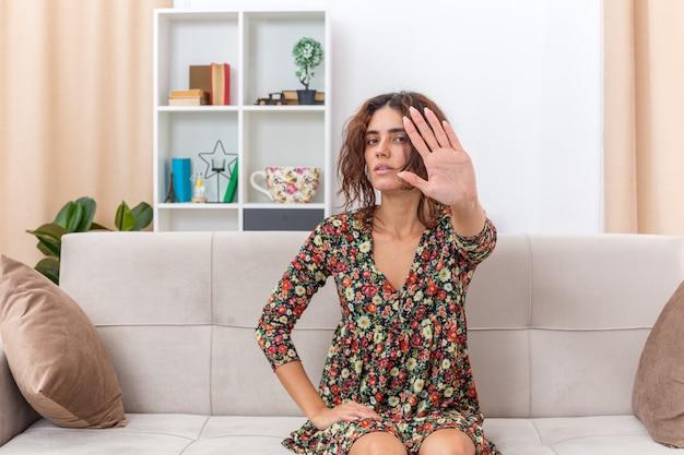 Jeune fille en robe à fleurs regardant avec un visage sérieux faisant un geste d'arrêt avec la main assise sur un canapé dans un salon lumineux