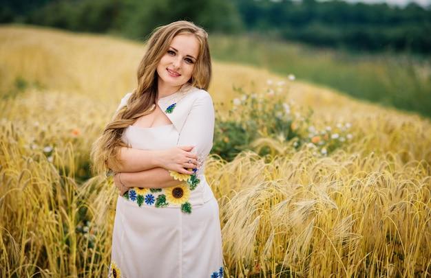 Jeune fille à la robe nationale ukrainienne posée au champ de la gerbe.