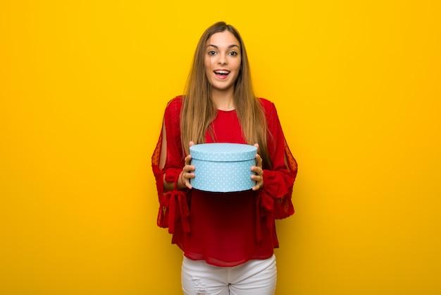 Jeune fille avec une robe rouge sur un mur jaune surpris car a reçu un cadeau