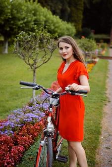 Jeune fille en robe rouge avec vélo rétro dans le parc