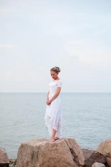 Jeune fille sur les rochers dans la mer