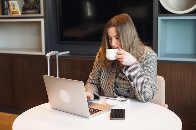 Une jeune fille rondelette attirante est assise dans un café en train de boire du café et travaille sur une photo de haute qualité pour ordinateur portable