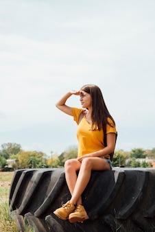 Jeune fille sur une roue de tracteur à la recherche de suite