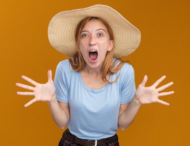 Jeune fille rousse agacée au gingembre avec des taches de rousseur portant un chapeau de plage tenant les mains ouvertes et criant sur quelqu'un qui regarde la caméra