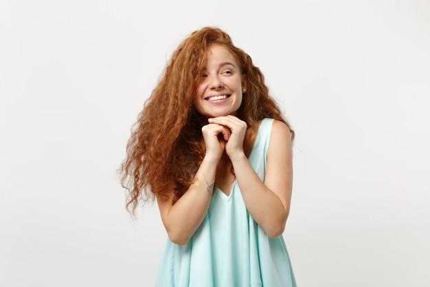 Jeune fille rousse assez souriante dans des vêtements légers décontractés posant isolé sur fond blanc en studio. concept de mode de vie des gens. maquette de l'espace de copie. mettez les mains sur le menton, en regardant de côté.