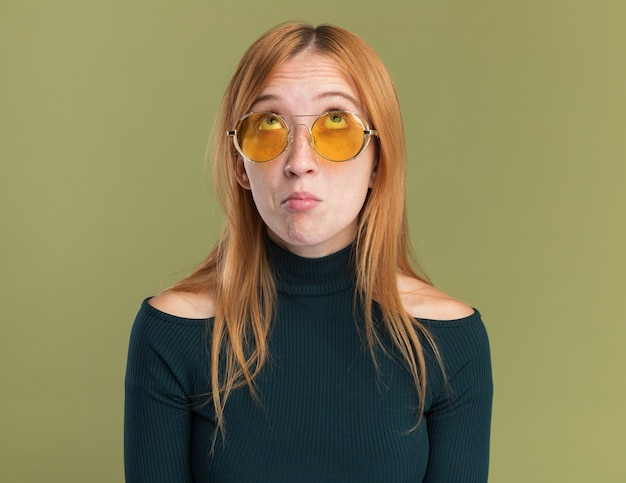 Jeune fille rousse au gingembre impressionnée avec des taches de rousseur dans des lunettes de soleil levant isolée sur un mur vert olive avec espace pour copie