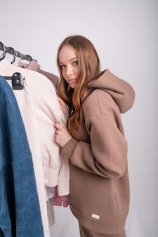 Jeune fille rousse caucasienne dans la salle d'exposition examine et choisit des vêtements