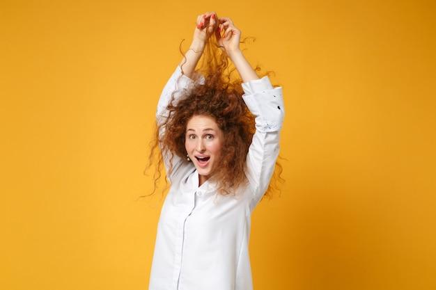 Jeune fille rousse choquée en chemise blanche posant isolée sur un mur orange jaune