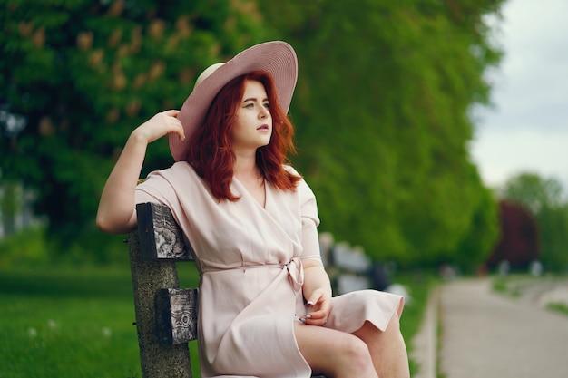 Une jeune fille rousse dans un grand chapeau rond et une robe rose assis sur un banc