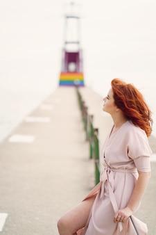 Jeune fille rousse dans un grand chapeau rond et robe rose assis sur le moorage près de l'océan