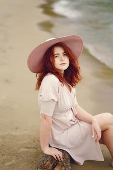 Une jeune fille rousse dans un grand chapeau rond et robe rose assis sur la plage près de l'océan
