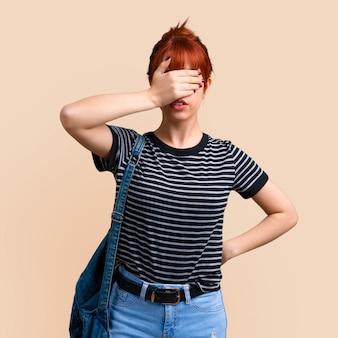 Jeune fille rousse étudiant couvrant les yeux par des mains sur fond ocre. retour à l'école
