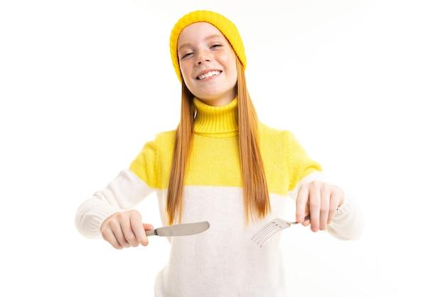 Jeune fille rousse européenne souriante tenant une fourchette et un couteau sur un fond de studio blanc.