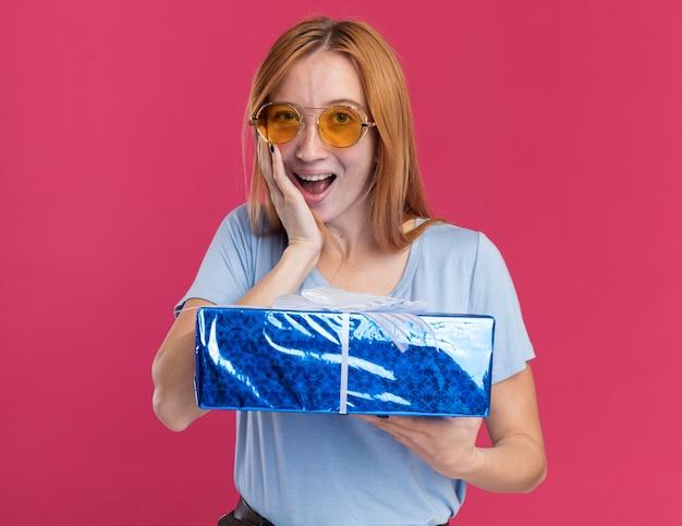 Une jeune fille rousse excitée au gingembre avec des taches de rousseur dans des lunettes de soleil met la main sur le visage et tient une boîte-cadeau