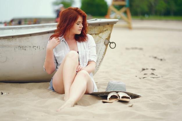 Une jeune fille rousse avec un grand chapeau rond assis sur le sable sur la plage près du bateau
