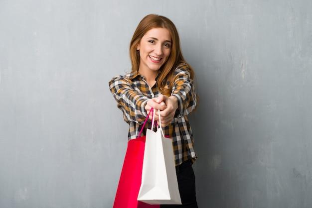 Jeune fille rousse sur mur grunge tenant beaucoup de sacs à provisions