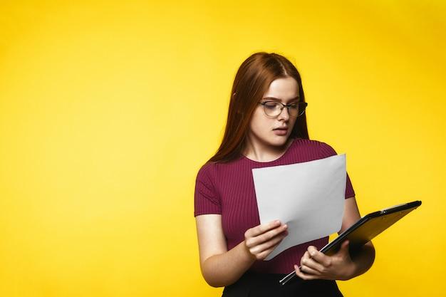 Jeune fille rousse regarde dans les documents et a l'air sérieux
