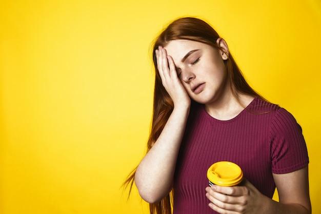 Jeune fille rousse regarde somnolent et tient une tasse avec du café debout