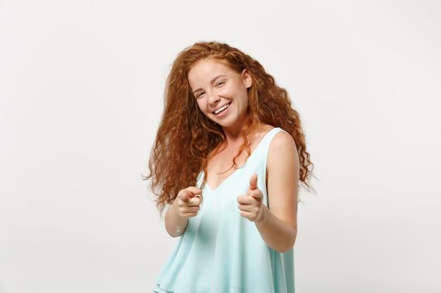 Jeune fille rousse souriante dans des vêtements légers décontractés posant isolé sur fond de mur blanc, portrait en studio. concept de mode de vie des gens. maquette de l'espace de copie. pointer l'index sur la caméra.