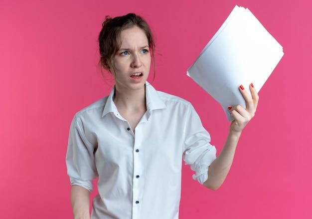 Jeune fille russe blonde agacée détient des feuilles de papier à côté isolé sur espace rose avec copie espace