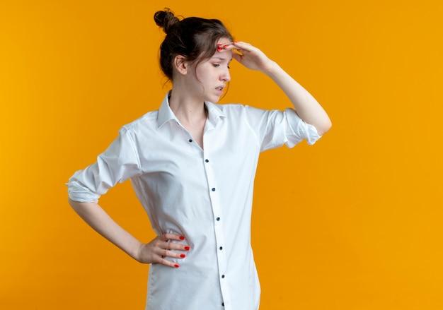 Jeune fille russe blonde agacée met la main sur le front à côté isolé sur espace orange avec copie espace