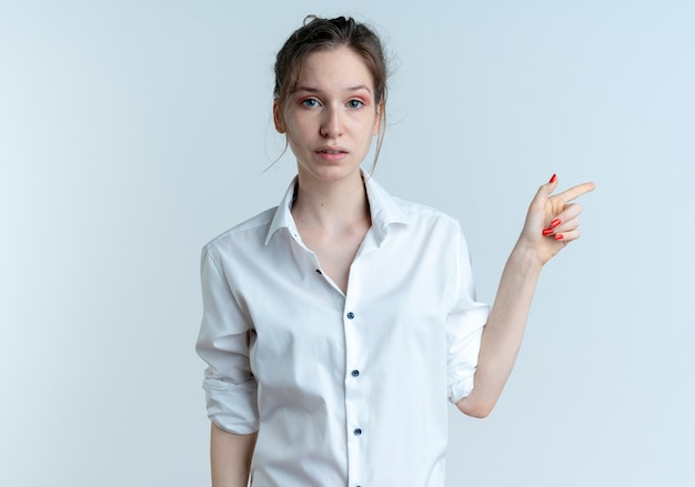 Jeune fille russe blonde anxieuse pointe sur le côté regardant la caméra
