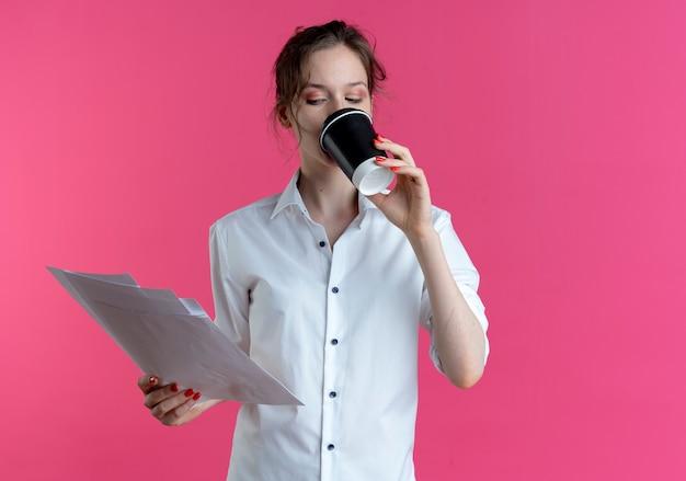 Jeune fille russe blonde confiante boit une tasse de café en regardant des feuilles de papier isolées sur un espace rose avec espace copie