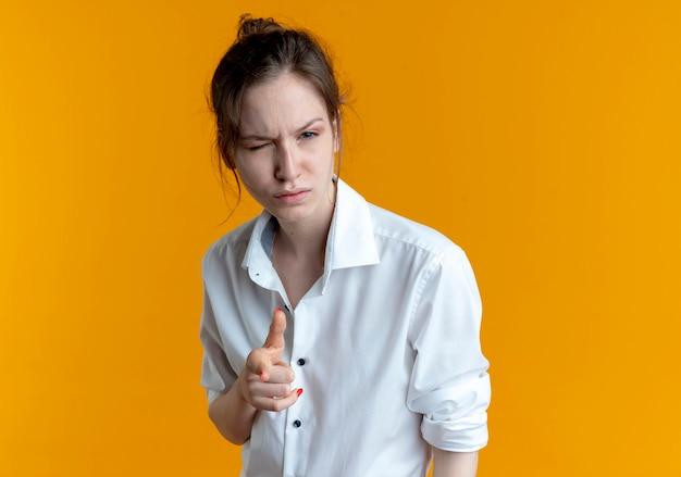 Jeune Fille Russe Blonde Confiante Cligne Des Yeux Pointant Sur La Caméra Sur L'orange Avec Copie Espace Photo gratuit