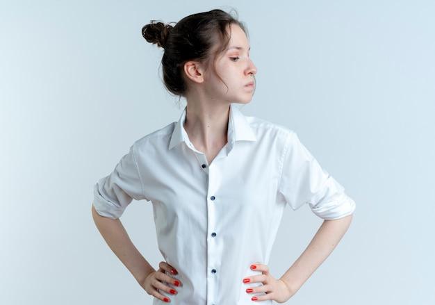 Jeune fille russe blonde confiante met les mains sur la taille à côté