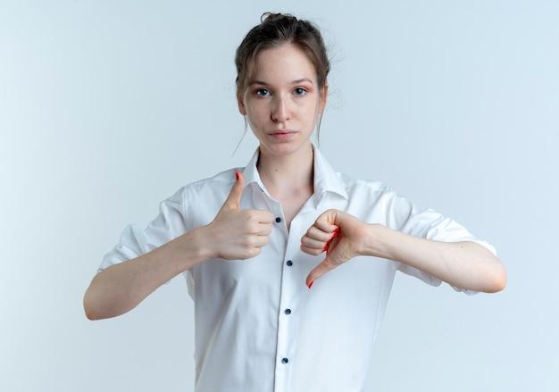 Jeune fille russe blonde confiante pouces vers le haut et pouces vers le bas isolé sur un espace blanc avec copie espace