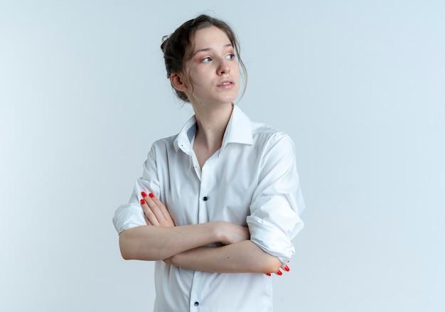 Jeune fille russe blonde confiante regarde le côté avec les bras croisés