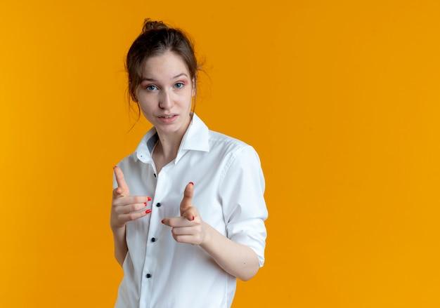 Jeune fille russe blonde confiante regarde et pointe la caméra isolée sur fond orange