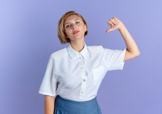 Jeune fille russe blonde confiante se pointe sur elle-même isolée sur fond violet avec copie espace