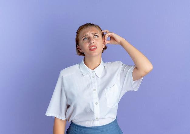 Jeune fille russe blonde confuse met la main sur la tête isolée sur fond violet avec copie espace