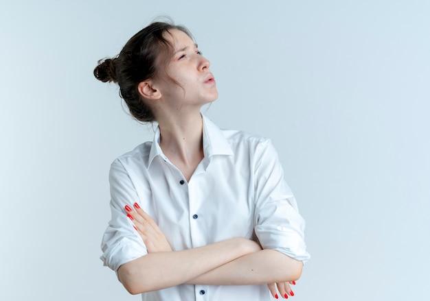 Jeune fille russe blonde confuse se tient avec les bras croisés à côté