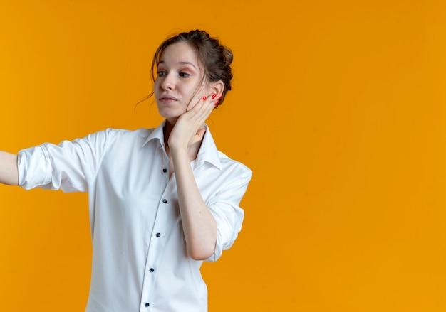 Jeune fille russe blonde heureuse met la main sur le visage à côté isolé
