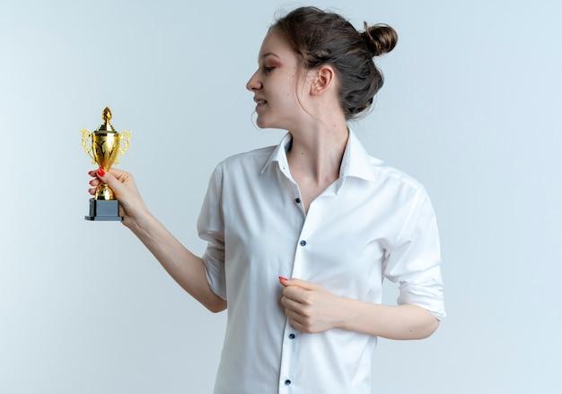 Jeune fille russe blonde heureuse tient et regarde la coupe du gagnant isolé sur fond blanc