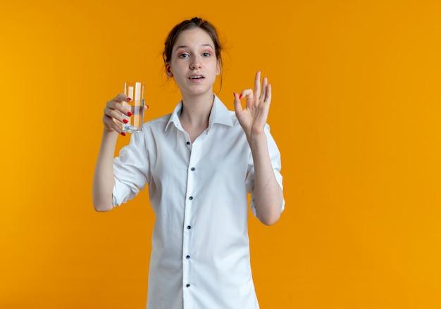Jeune fille russe blonde heureuse tient le verre d'eau gesticulant signe de la main ok isolé sur l'espace orange avec copie espace