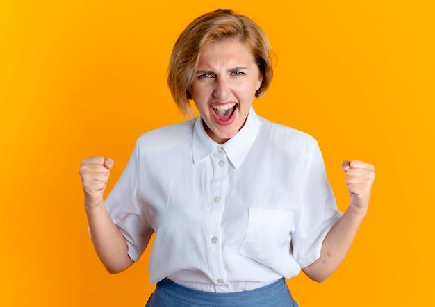 Jeune fille russe blonde joyeuse garde les poings isolés sur fond orange avec copie espace