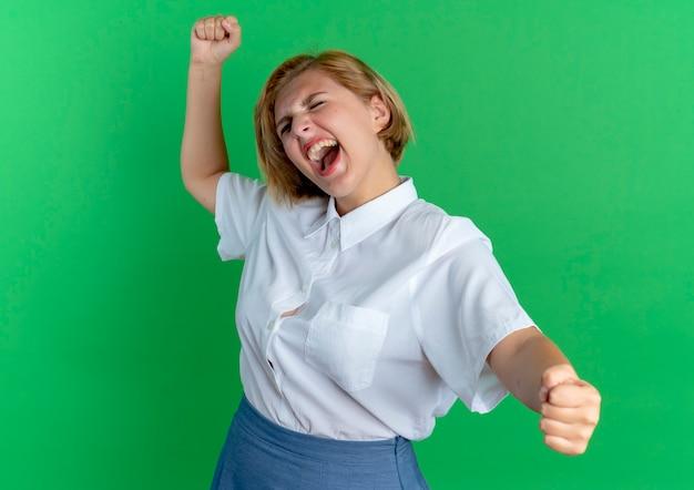 Jeune fille russe blonde joyeuse tient le poing de haut en bas isolé sur fond vert avec espace copie