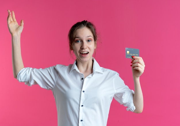 Jeune fille russe blonde surprise tient la carte de crédit et lève la main