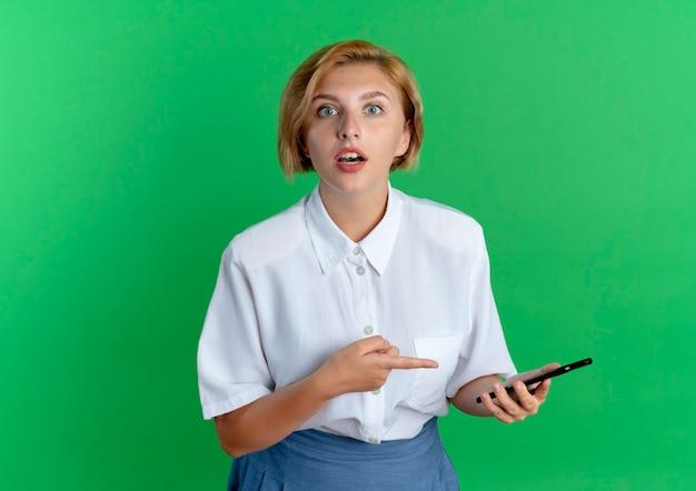 Jeune fille russe blonde surprise tient et pointe le téléphone en regardant la caméra isolée sur fond vert avec copie espace