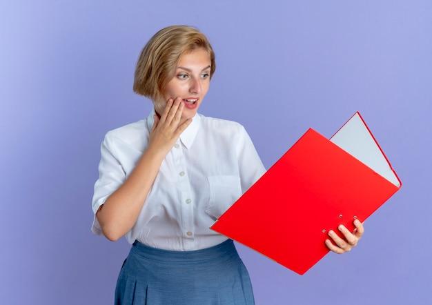 Jeune fille russe blonde surprise tient et regarde le dossier de fichiers met la main sur le visage isolé sur fond violet avec espace de copie