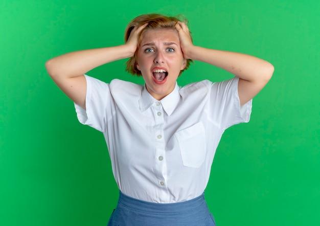 Jeune fille russe blonde surprise tient la tête regardant la caméra isolée sur fond vert avec copie espace