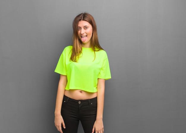 Jeune fille russe cool drôle et sympathique montrant la langue