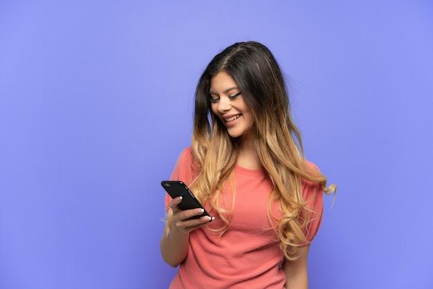 Jeune fille russe isolée sur fond bleu envoyant un message ou un e-mail avec le mobile