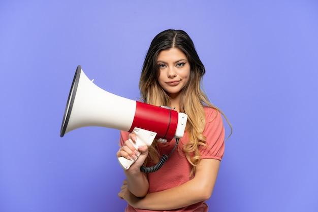 Jeune fille russe isolée sur fond bleu tenant un mégaphone et souriant