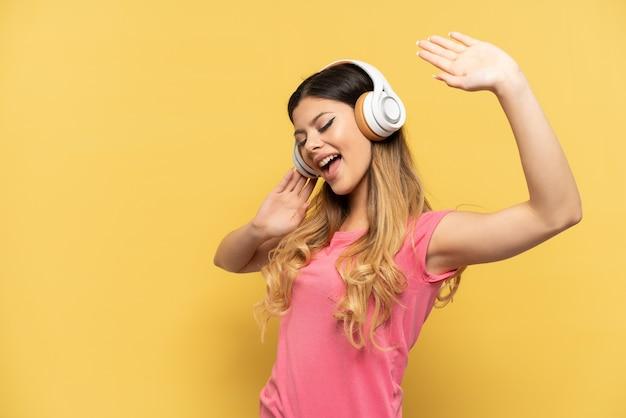 Jeune fille russe isolée sur fond jaune, écoutant de la musique et chantant