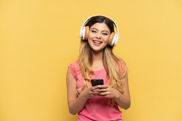 Jeune fille russe isolée sur fond jaune, écoutant de la musique avec un mobile et regardant à l'avant