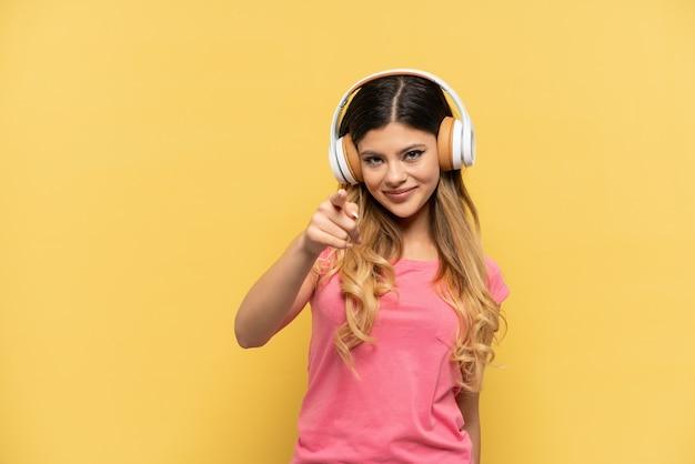 Jeune fille russe isolée sur fond jaune, écoutant de la musique et pointant vers l'avant